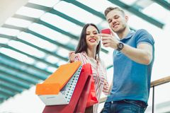 Young couple with shopping bags and smartphone talking in mall. Happy young couple with shopping bags and smartphone talking in mall Stock Photography