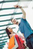 Young couple with shopping bags and smartphone talking in mall. Happy young couple with shopping bags and smartphone talking in mall Stock Image