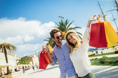 Young couple with shopping bags walking by the harbor of a touristic sea resort. Happy young couple with shopping bags walking by the harbor of a touristic sea royalty free stock photography