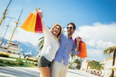 Young couple with shopping bags walking by the harbor of a touristic sea resort. Happy young couple with shopping bags walking by the harbor of a touristic sea royalty free stock photo