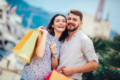 Young couple with shopping bags walking by the harbor of a touristic sea resort with boats on background. Happy young couple with shopping bags walking by the stock photography