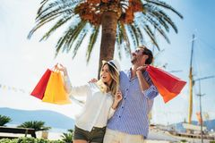 Young couple with shopping bags walking by the harbor of a touristic sea resort. Happy young couple with shopping bags walking by the harbor of a touristic sea stock images