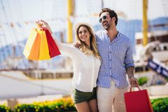 Young couple with shopping bags walking by the harbor of a touristic sea resort. Happy young couple with shopping bags walking by the harbor of a touristic sea royalty free stock images