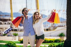 Young couple with shopping bags walking by the harbor of a touristic sea resort. Happy young couple with shopping bags walking by the harbor of a touristic sea royalty free stock photos