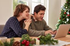 Young couple at home shopping online for christmas Stock Photos