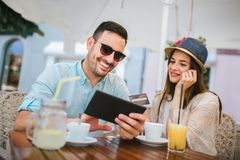 Young couple shopping online while sitting in a cafe. Happy young couple shopping online while sitting in a cafe stock images