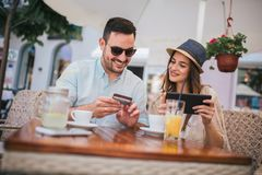 Young couple shopping online while sitting in a cafe. Happy young couple shopping online while sitting in a cafe royalty free stock image