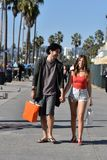 Young couple shopping on a boardwalk. Happy young couple shopping at an outdoor market in a tropical location stock images