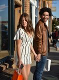 Happy young couple shopping. A young couple shopping on a sunny street royalty free stock photos