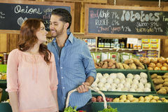 Happy young couple shopping together for vegetables in market Royalty Free Stock Images