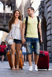Happy young couple in shorts walking through city Royalty Free Stock Image