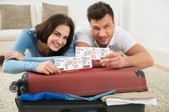 Happy young couple showing boarding pass Stock Photography