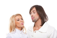 Young couple is showing tongues to each other Royalty Free Stock Photos