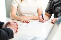 Happy young couple signing agreement or contract. Health insurance document, bank loan, mortgage or apartment rental paper. Woman and men having meeting with royalty free stock photos