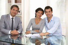 Happy young couple signing financial contract, looking camera Royalty Free Stock Photo