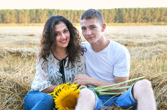 Happy young couple sit in wheaten field at evening, romantic people concept, beautiful landscape, summer season Royalty Free Stock Photo