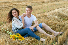 Happy young couple sit in wheaten field at evening, romantic people concept, beautiful landscape, summer season Royalty Free Stock Photography
