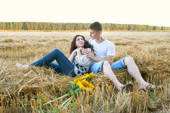 Happy young couple sit in wheaten field at evening, romantic people concept, beautiful landscape, summer season Stock Photo