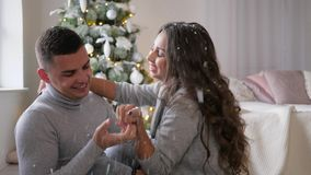 Happy young couple sits on floor in the room and kissing under confetti in slow motion near New Year tree. Happy young couple sits on the floor in the room and stock video footage