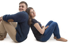 Happy young couple sitting back to back Royalty Free Stock Photos