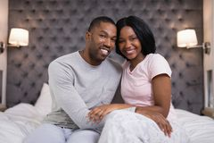 Happy young couple sitting on bed at home Stock Images