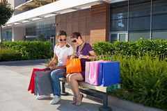 Young cheerful couple relaxing, carrying colorful shopping bags. Happy young couple sitting on a bench in front of a shopping mall with colorful shopping bags Royalty Free Stock Image
