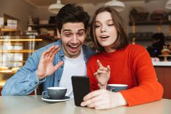 Happy young couple sitting at a cafe Stock Photos