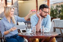Happy young couple sitting in a cafe and shopping online. Woman taking credit card from her boyfriend stock images