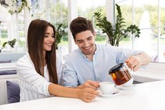 Happy young couple sitting at the cafe table. Drinking tea royalty free stock photos