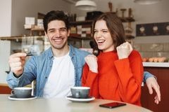 Happy young couple sitting at the cafe table Royalty Free Stock Images