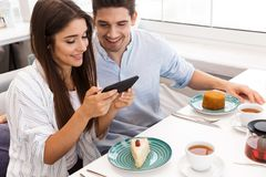 Happy young couple sitting at the cafe table. Having lunch, taking a photo of food royalty free stock photography