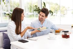 Happy young couple sitting at the cafe table. Having lunch, talking stock photography