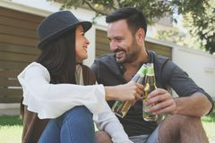 Happy young couple sitting in city park drinking beer, get toast Stock Images