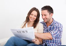 Happy young couple sitting on couch reading newspaper Stock Photos