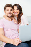 Happy young couple sitting on couch using laptop Stock Image
