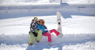 Happy young couple sitting on a deep shelf of snow Royalty Free Stock Photography