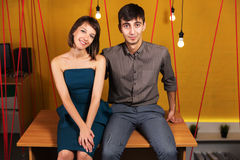 Happy young couple sitting on the desk in office Royalty Free Stock Photos