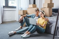 happy young couple sitting on floor of bedroom and using laptop while moving into