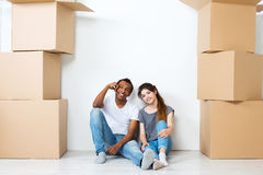 Happy young couple sitting on floor dreaming. Moving Stock Photos