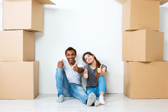 Happy young couple sitting on floor dreaming. Moving Royalty Free Stock Photos