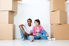 Happy young couple sitting on floor dreaming. Moving Stock Photography