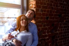 Happy Young Couple Sitting On Floor Looking Up While Dreaming Their New Home. Building in a developer royalty free stock image