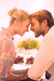 Happy young couple sitting in the garden enjoying wine together Royalty Free Stock Photography