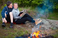 Happy young couple sitting near campfire and reading book royalty free stock photo