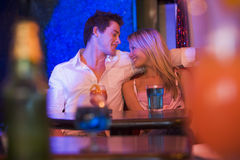 Happy young couple sitting in a nightclub, smiling Royalty Free Stock Photos