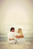 Happy Young Couple Sitting by the Ocean on the Beach stock image