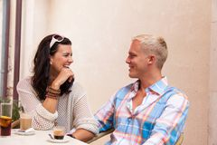 Happy young couple sitting outside cafe restaurant drinking coffee Stock Image