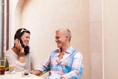 Happy young couple sitting outside cafe restaurant drinking coffee Royalty Free Stock Photo