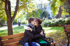 Happy young couple sitting on a park bench Royalty Free Stock Images
