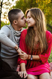 Happy young couple sitting in the park and hold hands in love. Affectionate happy young couple having fun in the city stock image